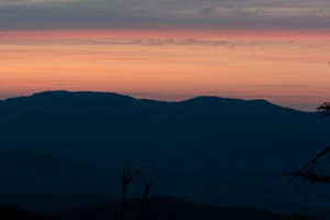 Pre-dawn light colors the mountains